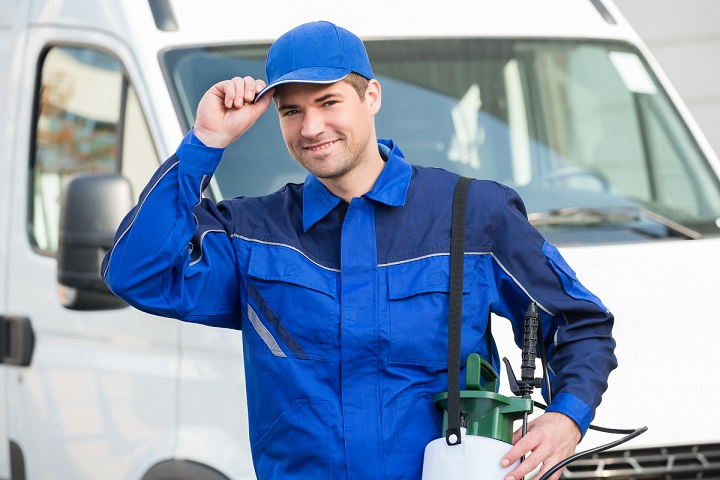 happy pest control company owner in blue uniform